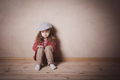 Sad child sitting on the floor Stock Images