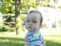 Sad child sitting on the green grass . Royalty Free Stock Images