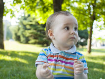 Sad child sitting on the green grass . Stock Image