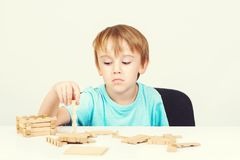 Sad child sitting at table. Child plays with construction toy blocks at the table. Sad bored boy build wooden house. Kid plays wit royalty free stock images