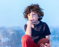 Sad child sitting on a window on a rainy day Stock Image