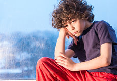 Sad child sitting on a window on a rainy day Royalty Free Stock Photos