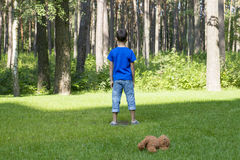 Sad child standing on the meadow. Brown teddy bear behind him. Boy looking to the forest or park. Sadness, fear. Sad child standing on the meadow. Brown teddy Royalty Free Stock Photo