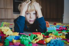 Sad child, stress and depression, exhaustion with toys scattered around. Boring at home royalty free stock photos