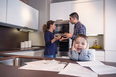 Sad child suffering and parents having discussion. Sad child suffering and his parents having hard discussion in a home kitchen by couple difficulties. Family Royalty Free Stock Images