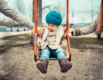 Divorce and  Separation concept. Sad child on a swing, inbetween her  divorced parents holding her separatedly Royalty Free Stock Images