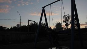 Sad child swinging on a swing on a dark sky background. child abuse, painful childhood stock footage