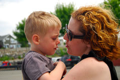 Sad child held by mother. Little boy upset after a fall at playground is comforted by his mother stock photography