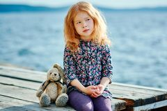 Sad child with a toy sitting on the pier near the water.  royalty free stock photo
