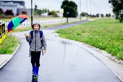 Free Sad Child Walking In Rubber Wellingtons On Wet Footpath. Royalty Free Stock Images - 78368569