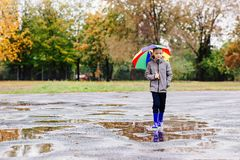 Sad child walking in rubber wellingtons on wet footpath. Stock Image