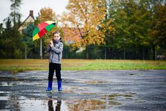 Sad child walking in rubber wellingtons on wet footpath. Stock Images