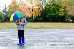 Sad child walking in rubber wellingtons on wet footpath. Royalty Free Stock Images