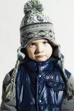 Sad child.winter fashion kids.fashionable little boy in cap. Portrait of sad child.winter fashion kids.fashionable little boy in cap royalty free stock images