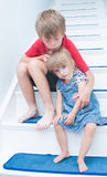 Sad Children. A sad brother and sister sitting on the stairs of the family home Royalty Free Stock Photos
