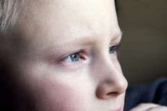 Sad children eyes. Close up - sad, upset blond boy (teen Royalty Free Stock Photography
