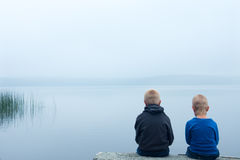Sad children in a foggy day. Two sad children (boys, brothers) sitting alone by lake in a foggy day, back view Stock Photo
