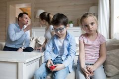 Sad children listen parents have angry fight at home headshot. Sad children listen parents have angry fight at home. Stressed kids looking at camera, mom and dad stock image