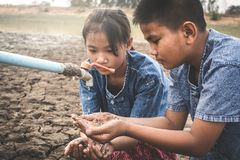Sad children want to drink some water on crack ground. Concept drought and shortage of water crisis Stock Photos