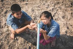 Sad children want to drink some water on crack ground. Concept drought and shortage of water crisis Royalty Free Stock Photography