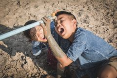 Sad children want to drink some water on crack ground. Concept drought and shortage of water crisis Stock Images