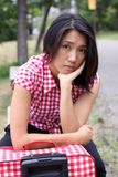 Sad Chinese girl waiting with suitcase outdoors Royalty Free Stock Images