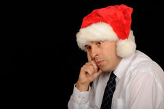 Sad Christmas businessman. Sad businessman wearing a Christmas cap, on a black studio background Royalty Free Stock Photos