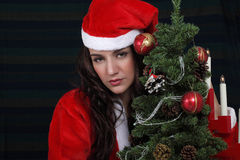 Sad Christmas girl. In Santa dress with lonely expression Royalty Free Stock Photography