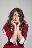 Sad Christmas woman in Santa costume resting head on hands looking at camera Stock Image
