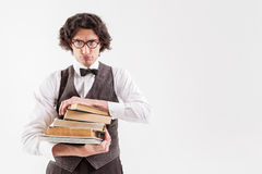 Sad clever male student with abundance of literature. It is too much for me. Dissatisfied young smart man is holding heap of books. His lips protruded in a sulky Stock Images