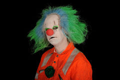Sad clown. Half body portrait of sad clown with bright green hair, isolated on black background Royalty Free Stock Photo
