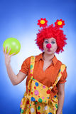Sad clown with a ball in hands on blue background Royalty Free Stock Photos