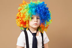 Sad clown boy with large colorful wig. Stock Photos