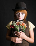Sad clown with flowers. Sad clown with bouqet on black royalty free stock photography