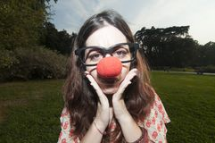 Sad clown girl with red nose at the park Royalty Free Stock Image