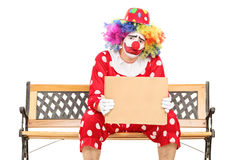 Sad clown holding a blank carton sign Stock Photos