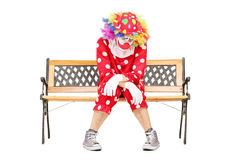 Sad clown sitting on a wooden bench Stock Photos