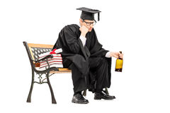 Sad college graduate drinking alcohol seated on bench. Isolated on white background Royalty Free Stock Image