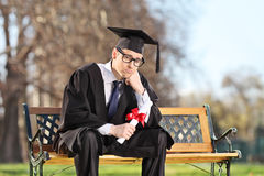 Sad college student sitting on a bench in park Stock Photography