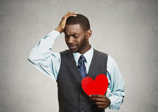 Sad company man holding red heart, crying Stock Images