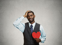 Sad company man holding red heart, crying Stock Photography