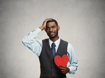 Sad company man holding red heart, crying Stock Photography