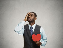 Sad company man holding red heart, loooking up Stock Photography
