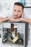 Sad computer engineer leaning on computer Stock Photography