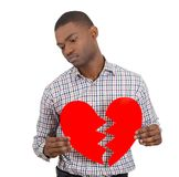 Sad confused man, holding broken heart in his hands Stock Photography