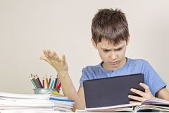 Sad, confused,surprised child with tablet computer sitting at table with books notebooks royalty free stock photography