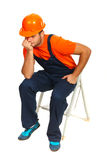 Sad constructor worker. Sitting and waiting on step ladder isolated on white background Royalty Free Stock Images