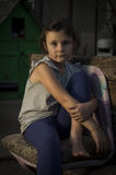 Sad countryside girl. Seven years old girl sitting sad in a chair in countryside in an evening light Royalty Free Stock Photography