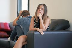 Sad couple after argument or breakup sitting on a sofa in the living room in a house indoor royalty free stock image