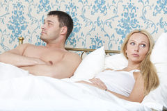 Sad couple in bed. Sad and unhappy couple lying in bed Royalty Free Stock Photography